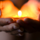 Hands holding candle--hope illuminates